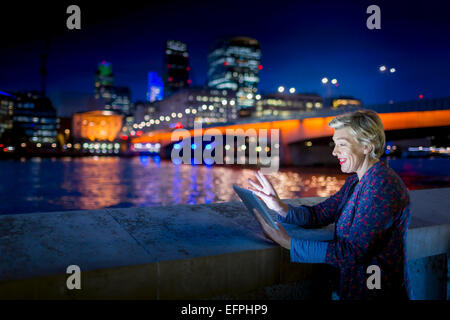 Mature businesswoman using digital tablet on Thames waterfront at night, London, UK - Stock Photo