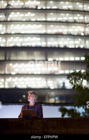 Mature businesswoman using digital tablet in front of office building at night, London, UK - Stock Photo