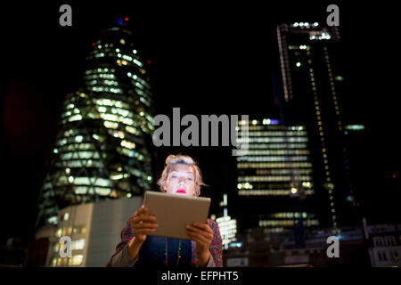 Mature woman in front of office buildings using digital tablet at night, London, UK - Stock Photo