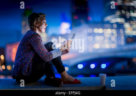 Mature businesswoman sitting on waterfront using  digital tablet at night, London, UK - Stock Photo