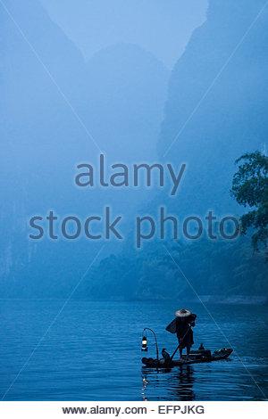 Silhouette of a cormorant fisherman paddling a lantern lit bamboo raft at dawn on the Li River, China, Asia - Stock Photo
