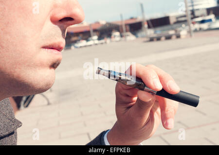 a young man vaping with an electronic cigarette - Stock Photo
