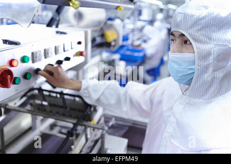Worker using machinery in ecigarette factory