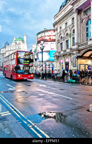London, United Kingdom - April 12, 2013: Piccadilly Circus neon signage reflected on street with typical double - Stock Photo