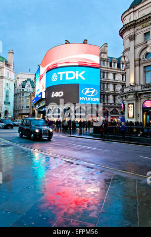 London, United Kingdom - April 12, 2013: famous Piccadilly Circus neon signage reflected on street with taxi in - Stock Photo