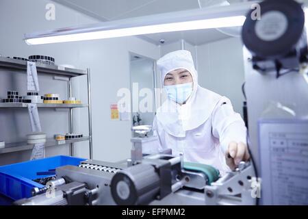 Workers using machinery in ecigarette factory