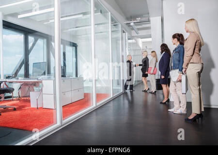 Women queueing outside interview room - Stock Photo