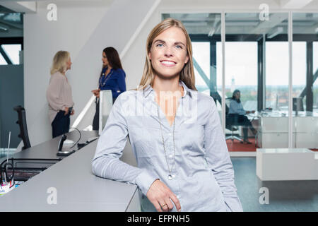 Mature woman wearing grey shirt in office, portrait - Stock Photo