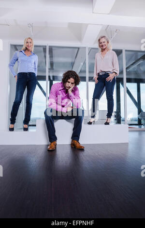 Man sitting on podium with head in hands with female colleagues - Stock Photo