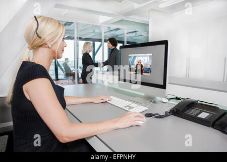 Mid adult woman on video call - Stock Photo