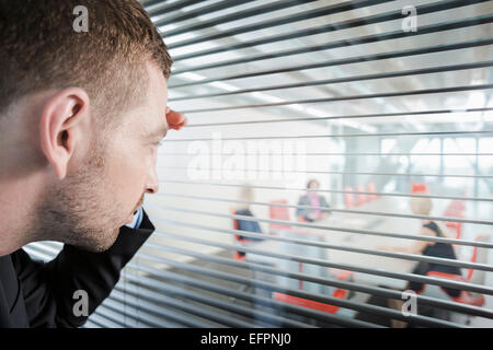 Man peering through window blinds - Stock Photo