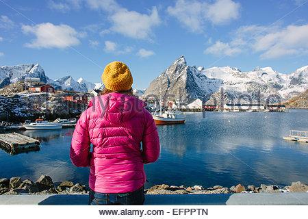 Woman by cod fishing village, Lofoten, Norway - Stock Photo