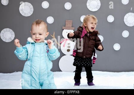 Baby girls with snow and snowman cutouts - Stock Photo