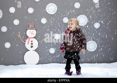 Baby girl with  snow and snowman cutouts - Stock Photo