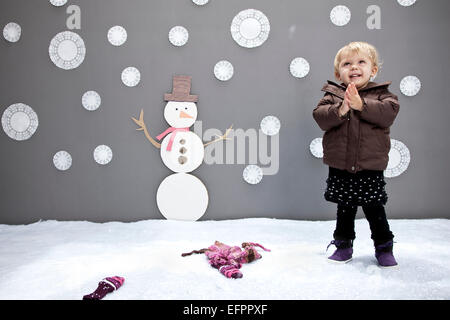 Baby girl with snowman and snowflake cutouts - Stock Photo