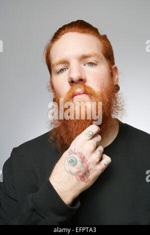 Studio portrait of young man with red hair stroking beard - Stock Photo