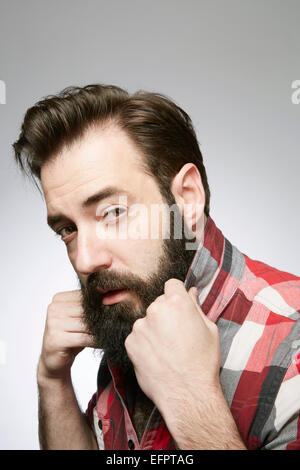 Studio portrait of posing bearded young man holding up shirt collar - Stock Photo