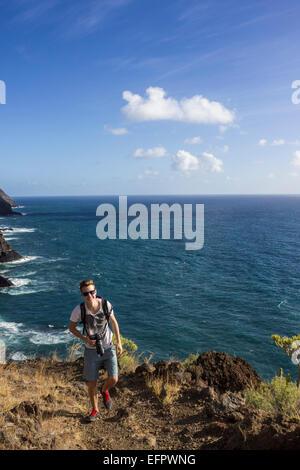 Hiker on a trail above the sea, cliffs, La Palma, Canary Islands, Spain - Stock Photo