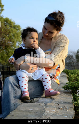 Mother holding her baby girl while they are enjoying a late afternoon in the park. - Stock Photo