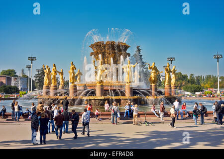 Tourists at the Friendship of the People Fountain at the All-Russia Exhibition Centre (VDNKh). Moscow, Russia. - Stock Photo