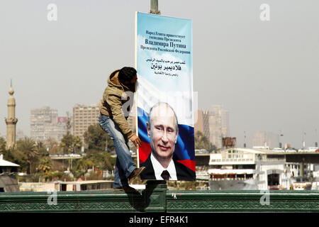 Cairo, Egypt. 9th Feb, 2015. An Egyptian worker adjusts a banner displaying the portrait of Russian President Vladimir - Stock Photo