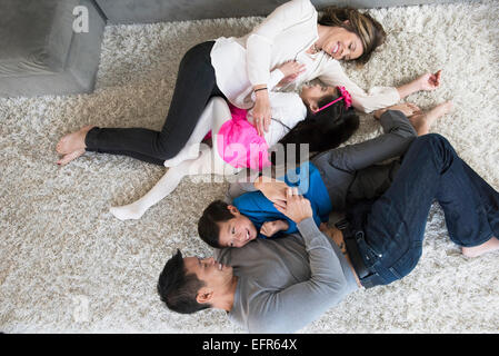 Overhead view of mature couple and two children play fighting on living room floor - Stock Photo
