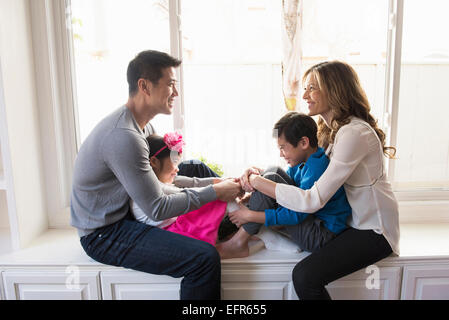 Mature couple and two children sitting on living room window seat - Stock Photo