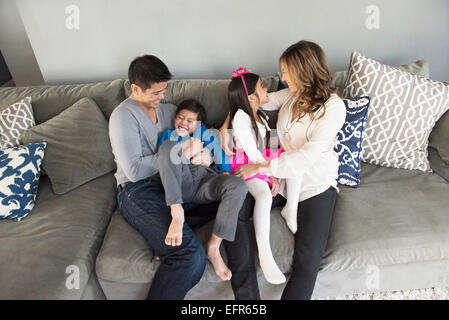 Mature couple and two children sitting on living room sofa - Stock Photo