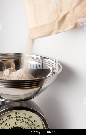 Weighing Wholemeal Bread Flour on Kitchen Scales - Stock Photo