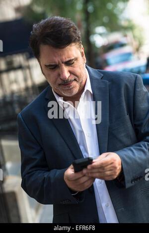 Mature businessman walking on street texting on smartphone - Stock Photo