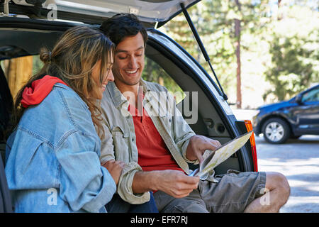 Young couple sitting on car boot looking at map, Los Angeles, California, USA - Stock Photo
