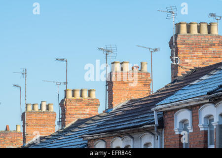 The rooftops, chimneys & TV aerials of  typical Victorian, terraced homes in a UK, Suburban street on a clear day - Stock Photo