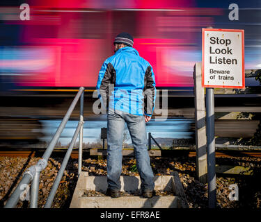 Man standing at rural level crossing as train speeds past - Stock Photo