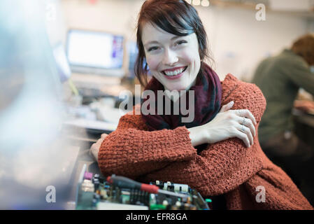 Computer Repair Shop. A woman smiling and leaning on a workshopcounter. - Stock Photo