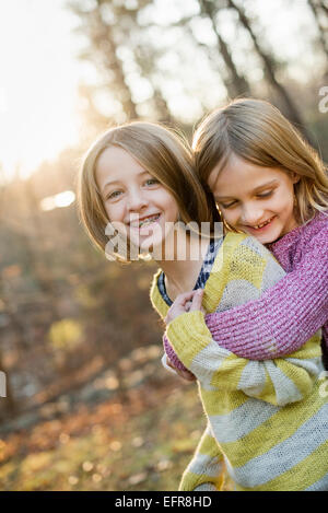 Two smiling girls in a forest, hugging each other. - Stock Photo