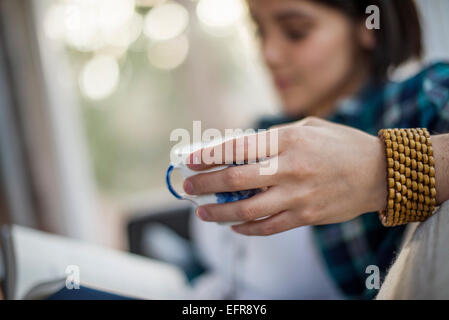 Close up of a woman's hand holding a tea cup, wearing a bracelet. - Stock Photo