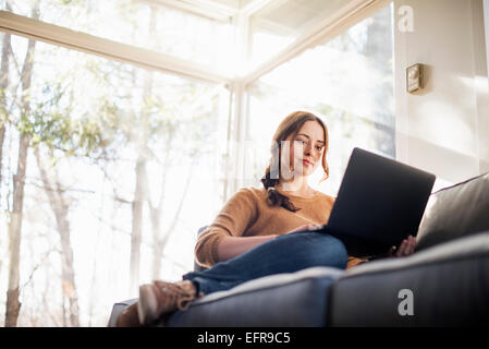 Low angle view of a woman sitting on a sofa looking at her laptop. - Stock Photo