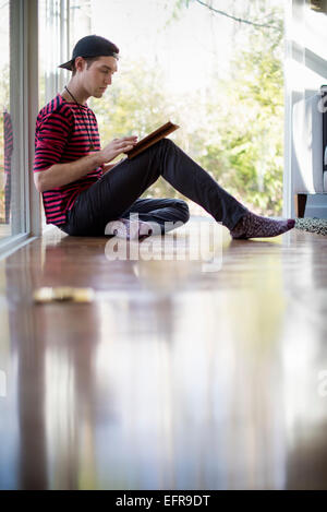 Man wearing a baseball cap backwards, sitting on the floor in a living room, looking at a digital tablet. - Stock Photo
