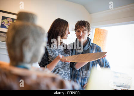 Smiling couple standing in a living room, woman holding a wooden tray. - Stock Photo