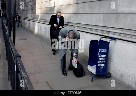 While holding a conversation on his smartphone, a stooping gent struggles to slide a free copy of the Evening Standard - Stock Photo
