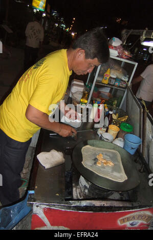 Vertical portrait of a street vendor busy making fresh pancakes on the roadside at night - Stock Photo