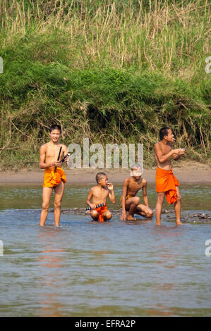 Vertical portrait of young apprentice Buddhist monks along the banks of the Mekong river. - Stock Photo