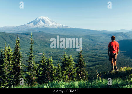 Male hiker on a mountain summit, looking at the landscape towards Mount Hood - Stock Photo