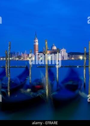 Riva degli Schiavoni and the Piazza San Marco island and church of San Giorgio Maggiore. Gondolas moored at dusk. - Stock Photo