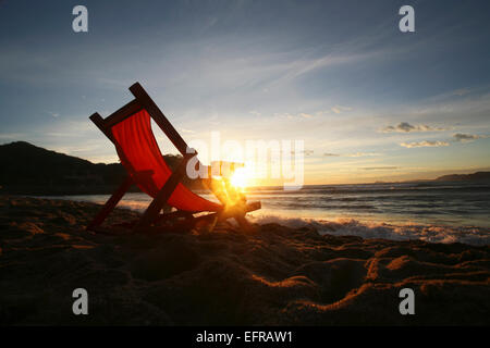 A chair on the sand facing the water. - Stock Photo