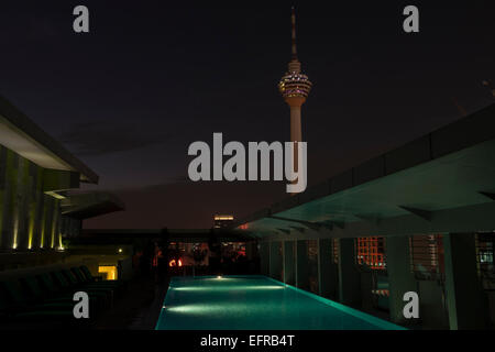 The KL Tower seen from the rooftop of a nearby building in Kuala Lumpur, Malaysia, at night. Swimming pool in foreground. - Stock Photo