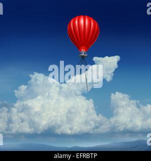 Aim high business success concept as a red hot air balloon lifting up a cumulus cloud shaped as an arrow metaphor - Stock Photo