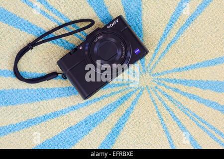 Sony RX100 II digital camera on a beach towel - Stock Photo