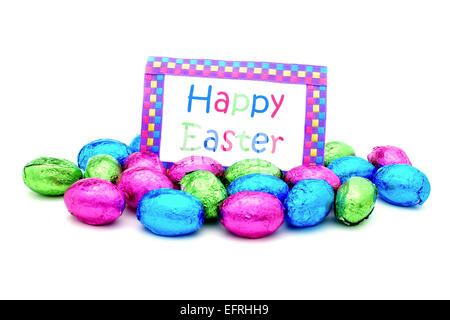 Pile of colorful chocolate eggs with Happy Easter card over white - Stock Photo