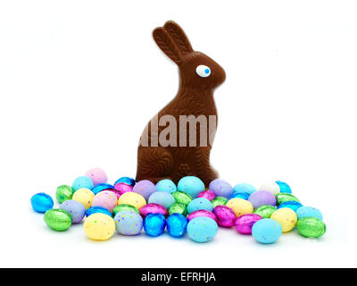 Chocolate Easter bunny with pile of colorful eggs over white - Stock Photo